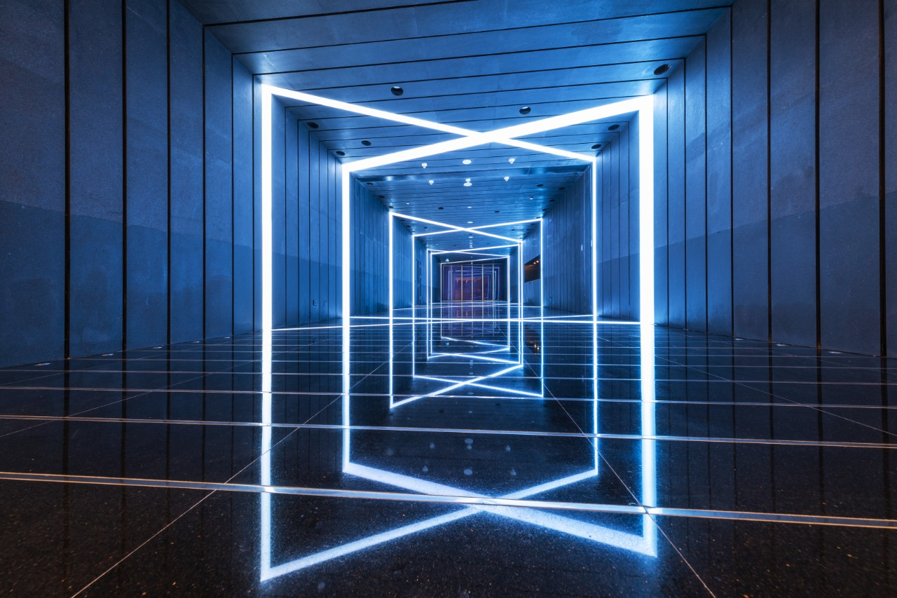 a metal paneled hallway with a light fixture that is in the shape of an x